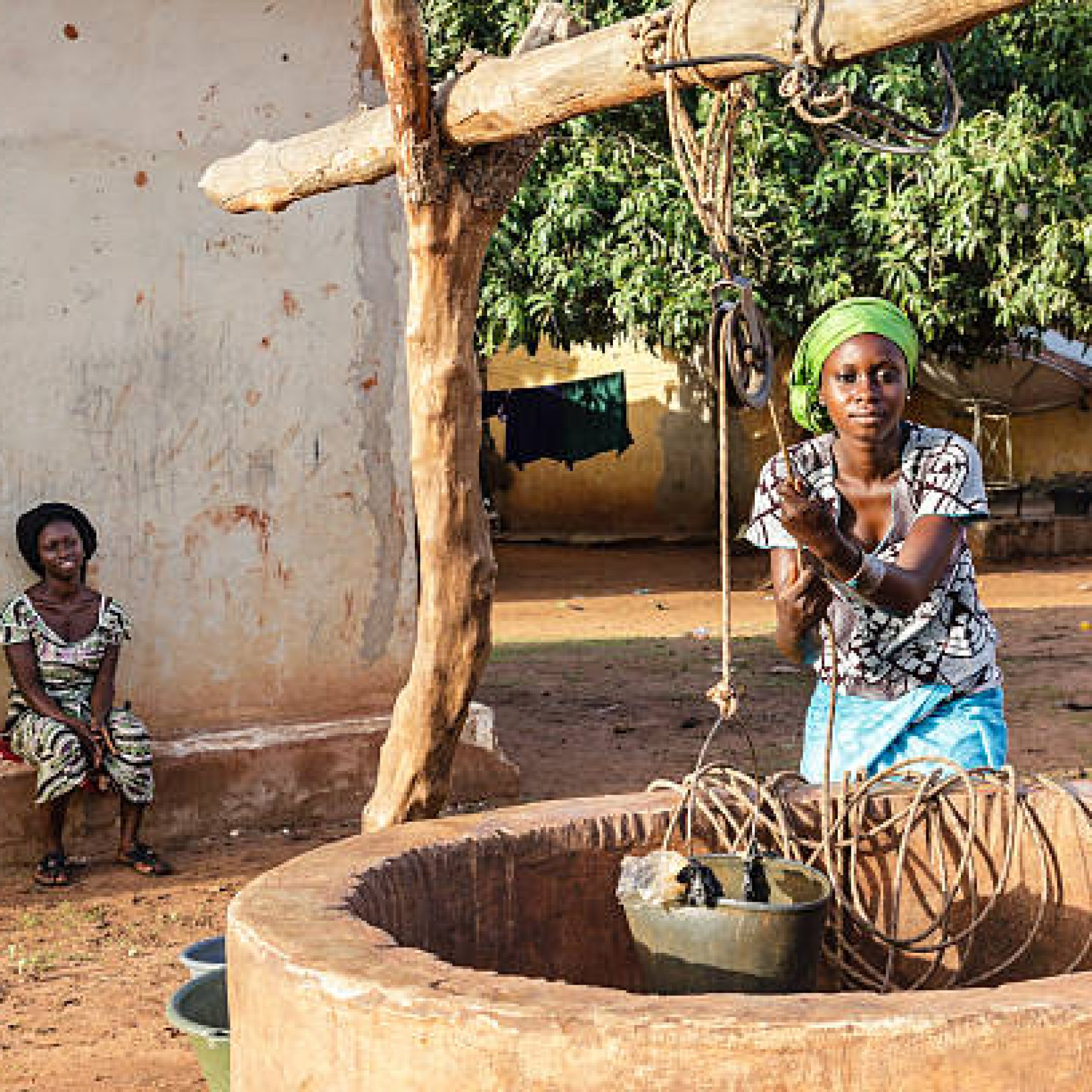 Two African women extracting water of