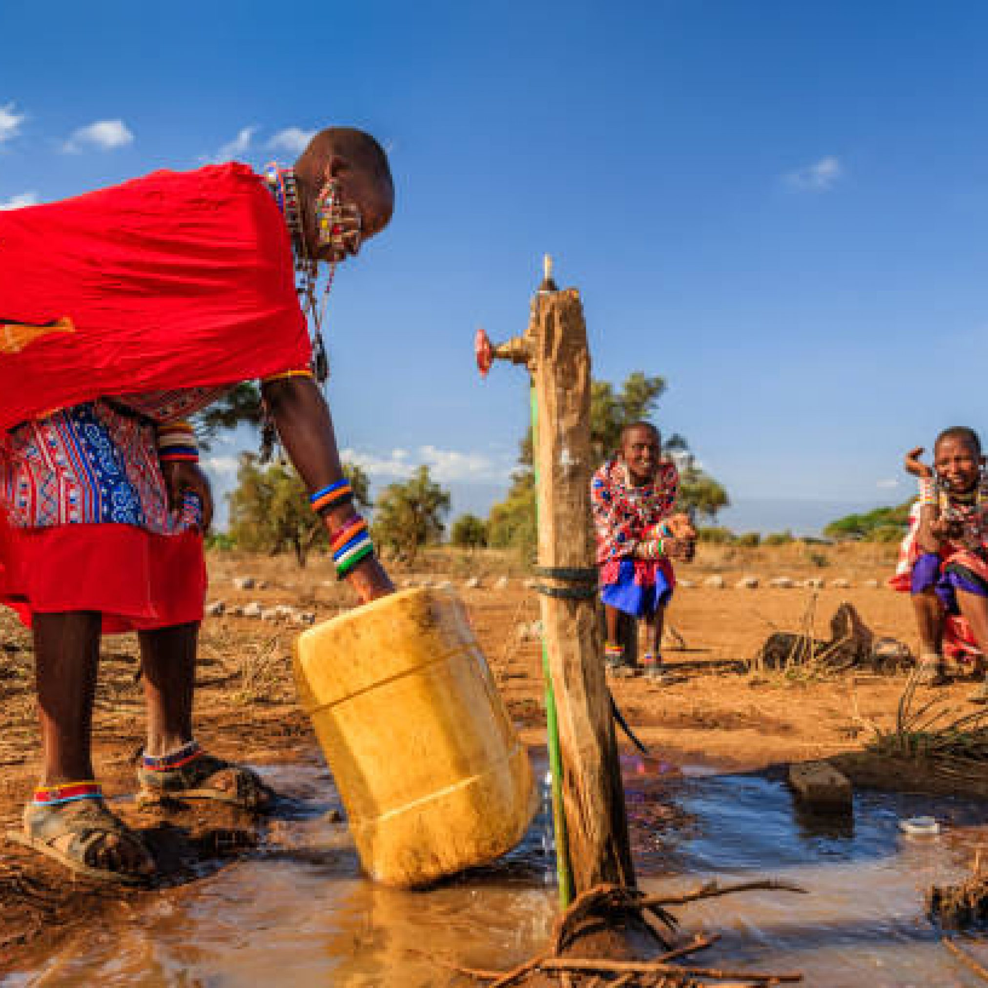 African woman from Maasai tribe collecting water to the tank, Kenya, Africa. When she finish filling the tank, she will carry water on her back to the village. African women and also children often walk long distances through the savanna to bring back containers of water. Some tourist camps cooperating with nearby villages and allow local people to use their water. Maasai tribe inhabiting southern Kenya and northern Tanzania, and they are related to the Samburu.